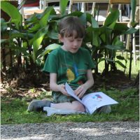 Boy sitting under a tree reading the book his dad just purchased for him - Alabama Book Festival 2015