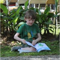 Boy sitting under a tree reading the book his dad just purchased for him- Alabama Book Festival 2015